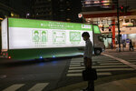 A man wearing a face mask wait at a crosswalk as a truck carrying a signs by the local government showing how to avoid spreading the COVID-19 makes a turn on a street, Thursday, Sept. 17, 2020, in Tokyo. (AP Photo/Kiichiro Sato)