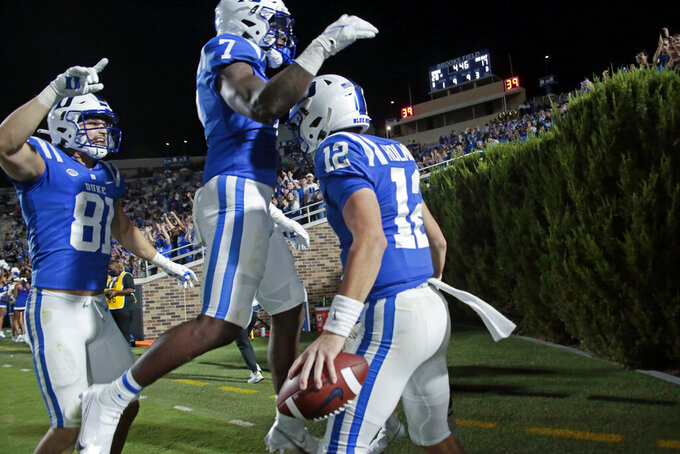 Duke quarterback Gunnar Holmberg (12) celebrates his touchdown run against North Carolina A&T with tight end Nicky Dalmolin (81) and running back Jordan Waters (7) during the second half of an NCAA college football game in Durham, N.C., Friday, Sept. 10, 2021. (AP Photo/Chris Seward)