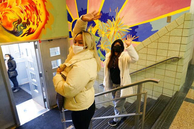 Two students right, wave goodbye to teachers and counselors after attending an in-person blended learning session at West Brooklyn Community High School, Wednesday, Nov. 18, 2020, in the Brooklyn borough of New York, after the school's principal announced that the school would be closed until further notice due to rising cases of coronavirus in the city. New York City Mayor Bill de Blasio said Wednesday he's shuttering schools to try to stop the renewed spread of the coronavirus. This is the third time the high school has had to close, with the most recent closure due to an outbreak in the immediate neighborhood, although the school has had no reported cases. (AP Photo/Kathy Willens)