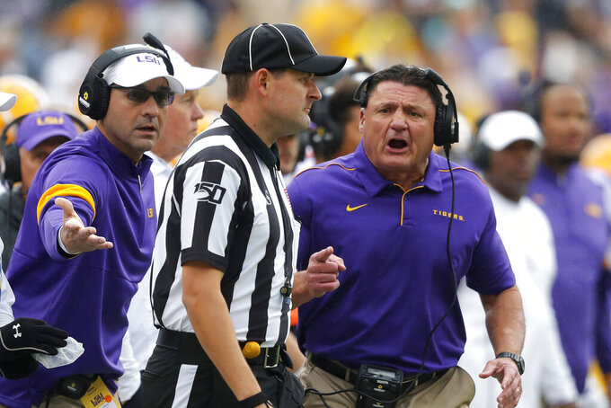 LSU head coach Ed Orgeron, right, challenges an official in the first half of an NCAA college football game against Auburn in Baton Rouge, La., Saturday, Oct. 26, 2019. (AP Photo/Gerald Herbert)