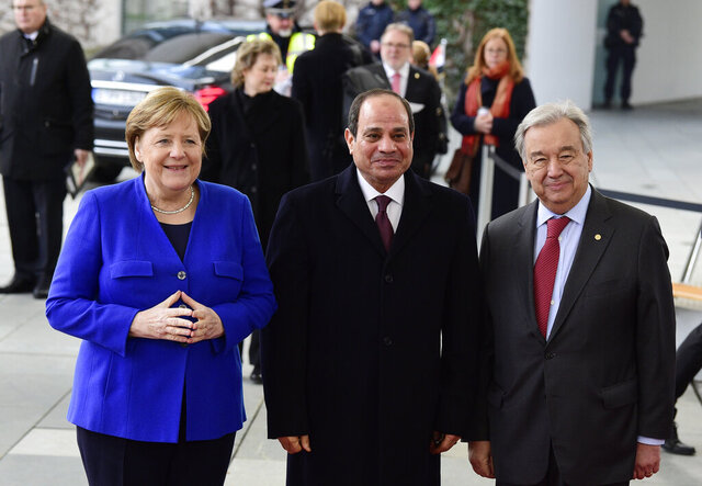 German Chancellor Angela Merkel, left, greets United Nations Secretary General Antonio Guterres, right, and Egypt's President Abdel Fattah al-Sisi, center, during arrivals for a conference on Libya at the chancellery in Berlin, Germany, Sunday, Jan. 19, 2020. German Chancellor Angela Merkel hosts the one-day conference of world powers on Sunday seeking to curb foreign military interference, solidify a cease-fire and help relaunch a political process to stop the chaos in the North African nation. (AP Photo/Jens Meyer)