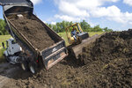 Plaquemines Parish road crews add more dirt to the top of a levee near the Mississippi River levee, back, and the St. Bernard Parish line as they prepare for potential flooding from Tropical Storm Barry in Braithwaite, La., on Thursday, July 11, 2019.  (Chris Granger/The Advocate via AP)