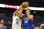 Orlando Magic forward Aaron Gordon (00) and Los Angeles Clippers center Ivica Zubac (40), from Croatia, battle for a rebound during the first quarter of an NBA basketball game in Orlando, Fla., Sunday, Jan. 26, 2020. (AP Photo/Reinhold Matay)