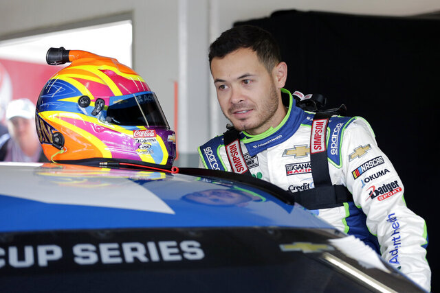 FILE - In this Feb, 8, 2020, file photo, Kyle Larson climbs into his car as he gets ready for a NASCAR auto race practice at Daytona International Speedway, in Daytona Beach, Fla. Larson will be back in NASCAR next season driving the flagship No. 5 Chevrolet for Hendrick Motorsports. Larson signed a multi-year contract Wednesday morning, Oct. 28, 2020, with Hendrick that ended his seven-month banishment from NASCAR for using a racial slur while playing an online racing game. (AP Photo/Terry Renna, File)