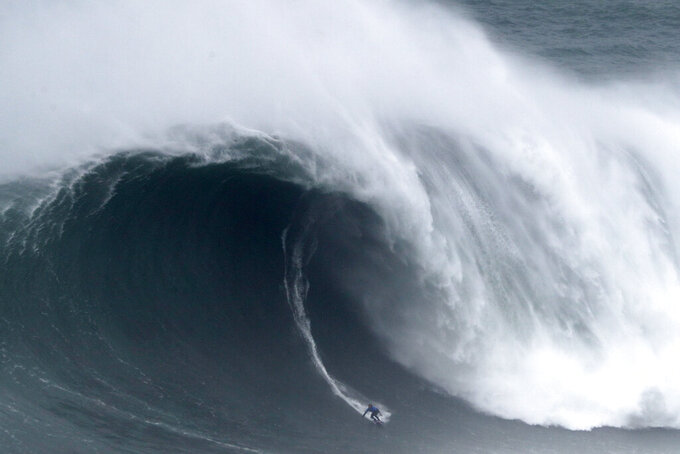 Kai Lenny from Hawaii rides a wave during the Nazare Tow Surfing Challenge at Praia do Norte or North Beach in Nazare, Portugal, Tuesday, Feb. 11, 2020. (AP Photo/Armando Franca)