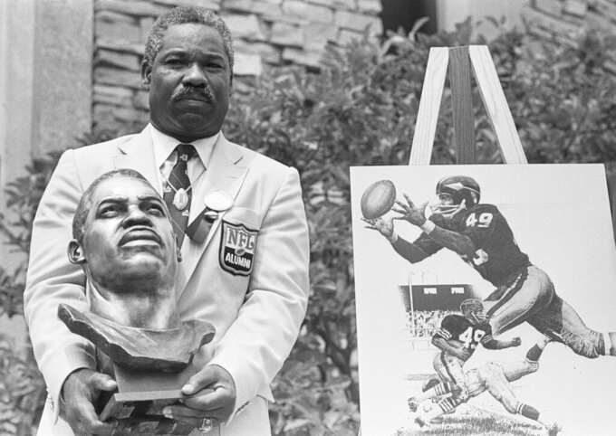 FILE - In this July 30, 1983, file photo, former Cleveland Browns and Washington Redskins halfback and wide receiver Bobby Mitchell poses with his bronze bust after being inducted into the Pro Football Hall of Fame in ceremonies in Canton, Ohio.    The Washington Redskins will retire the jersey of Mitchell and rename the lower level of FedEx Field for him, replacing former owner George Preston Marshall.  The team, which is being pressured to change its name during the ongoing national reckoning over racism, said Saturday, June 20, 2020,  that the No. 49 will become on the second in the franchise's 88-year history to be retired.   (AP Photo/Gus Chan, File)