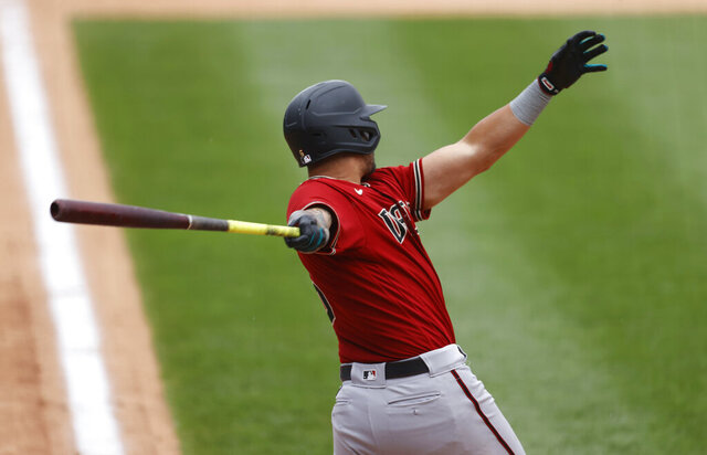 Arizona Diamondbacks' David Peralta follows the flight of his double to drive in three runs off Colorado Rockies relief pitcher Tyler Kinley in the seventh inning of a baseball game Wednesday, Aug. 12, 2020, in Denver. (AP Photo/David Zalubowski)
