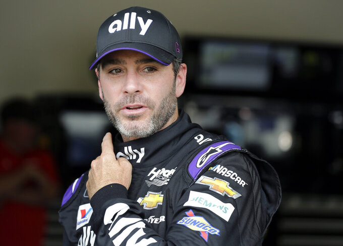 FILE - In this Feb. 16, 2019 file photo, Jimmie Johnson leaves his garage after NASCAR auto racing practice at Daytona International Speedway in Daytona Beach, Fla. Johnson plans to run in the Boston Marathon on Monday, April 15. (AP Photo/Terry Renna, File)