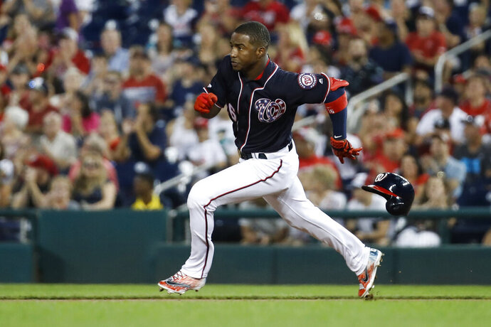 Washington Nationals' Victor Robles loses his helmet as he runs to second base for a double during the second inning of the team's baseball game against the Miami Marlins at Nationals Park, Friday, Aug. 30, 2019, in Washington. (AP Photo/Alex Brandon)
