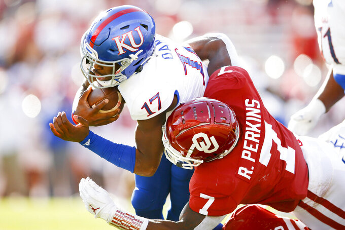Oklahoma defensive end Ronnie Perkins (7) tackles Kansas quarterback Jalon Daniels (17) during an NCAA college football game in Norman, Okla., Saturday, Nov. 7, 2020. (Ian Maule/Tulsa World via AP)