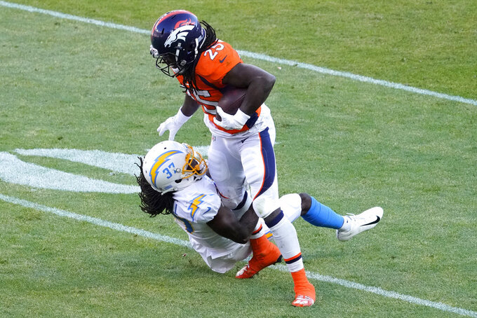 Denver Broncos running back Melvin Gordon (25) is hit by Los Angeles Chargers cornerback Tevaughn Campbell (37) during the first half of an NFL football game, Sunday, Nov. 1, 2020, in Denver. (AP Photo/Jack Dempsey)
