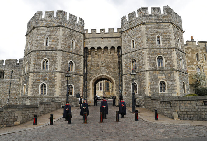 The King Henry VIII gate at Windsor Castle Windsor, England, Tuesday, April 13, 2021, guarded by armed police and casket wardens. Britain's Prince Philip, husband of Queen Elizabeth II, died Friday April 9 aged 99. His funeral service will take place on Saturday at Windsor Castle. (AP Photo/Alastair Grant)
