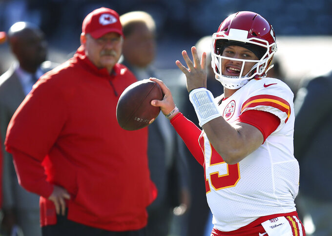 FILE - In this Dec. 2, 2018, file photo, Kansas City Chiefs coach Andy Reid, left, watches quarterback Patrick Mahomes (15) warm up for the team's NFL football game against the Oakland Raiders in Oakland, Calif. The Chiefs (12-4) get this week to rest and relax, the byproduct of earning that first-round bye. They will learn this weekend whether they will face the Colts, Ravens or Chargers in the divisional round on Jan. 12, the first of what they hope will be two games at Arrowhead Stadium before the Super Bowl. (AP Photo/Ben Margot, File)