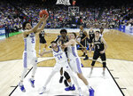 Kentucky's EJ Montgomery, left, grabs a Wofford rebound as Tyler Herro (14) holds back Wofford players during the first half of a second-round game in the NCAA men's college basketball tournament in Jacksonville, Fla., Saturday, March 23, 2019. (AP Photo/Stephen B. Morton)