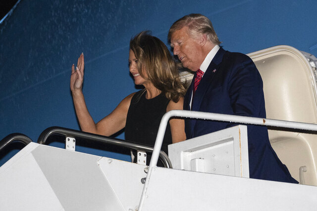 President Donald Trump, accompanied by first lady Melania Trump, steps off Air Force One at the Palm Beach International Airport, Friday, Feb. 14, 2020, in West Palm Beach, Fla. (AP Photo/Alex Brandon)
