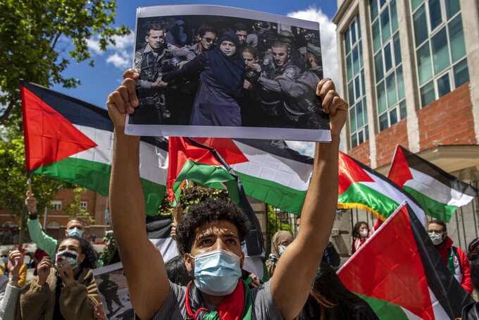 Protesters shout slogans and wave Palestinian flags in support of Palestinians during the latest round of violence, outside the Israeli embassy in Madrid, Spain, Tuesday, May 11, 2021. (AP Photo/Manu Fernandez)