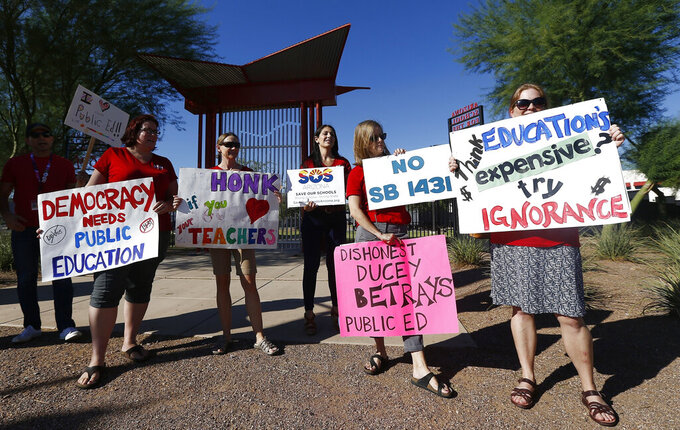 FILE - In this Aug. 24, 2017, file photo, members of Save Our Schools Arizona protest at the Arizona School for the Arts as Arizona Gov. Doug Ducey tours the school in Phoenix. A program announced by Arizona's Republican governor last month to give private school vouchers to students whose parents object to school mask requirements has seen a surge of applications, with twice as many either completed or started than can be funded with the $10 million in federal coronavirus relief cash he earmarked for the program. (AP Photo/Ross D. Franklin, File)