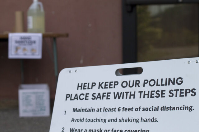 A sign reminds voters to socially distance while voting in the state's primary, election Tuesday, Sept. 8, 2020, outside Hopkinton Middle-High School in Hopkinton, N.H. (AP Photo/Holly Ramer)