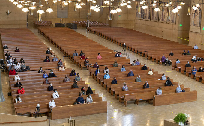 FILE - In this Sunday, June 7, 2020, file photo, a hundred faithful sit while minding social distancing, listening to Los Angeles Archbishop Jose H. Gomez celebrate Mass at Cathedral of Our Lady of the Angels, the first Mass held in English at the site since the re-opening of churches, in downtown Los Angeles.  The Supreme Court is telling California it can't enforce a ban on indoor church services because of the coronavirus pandemic. The high court issued orders late Friday, Feb. 5, 2021,  in two cases where churches had sued over coronavirus-related restrictions in the state(AP Photo/Damian Dovarganes, File)