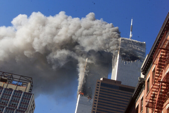 FILE - In this Sept. 11, 2001, file photo, smoke rises from the burning twin towers of the World Trade Center after hijacked planes crashed into the towers, in New York City. The coronavirus pandemic has reshaped how the U.S. is observing the anniversary of 9/11. The terror attacks' 19th anniversary will be marked Friday, Sept. 11, 2020, by dueling ceremonies at the Sept. 11 memorial plaza and a corner nearby in New York. (AP Photo/Richard Drew, File)
