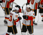 Calgary Flames left wing Johnny Gaudreau (13) is congratulated by defenseman Rasmus Andersson (4) after Gaudreau scored against the Dallas Stars during the shootout in an NHL hockey game in Dallas, Thursday, Oct. 10, 2019. Calgary won 3-2. (AP Photo/Michael Ainsworth)