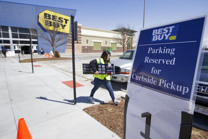 FILE - A Best Buy employee delivers an item to a waiting client in Omaha, Neb., Wednesday, April 15,  2020. Best Buy, the nation's largest consumer electronics chain, will require customers to wear face coverings at all of its stores nationwide, even in states or localities that don't require them to do so. The company said Tuesday, July 14, 2020 it will provide a face covering if a customer doesn't have one, and small children and those unable to wear one for health reasons may enter without one. (AP Photo/Nati Harnik)