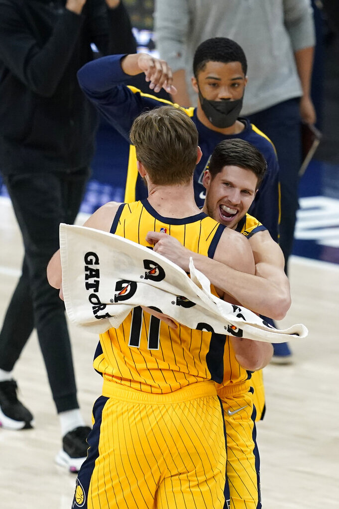 Indiana Pacers' Domantas Sabonis (11) and Doug McDermott (20) celebrate following an NBA basketball game against the Philadelphia 76ers, Tuesday, May 11, 2021, in Indianapolis. Indiana won 103-94. (AP Photo/Darron Cummings)