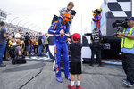 With son Hudson on his shoulders, Joey Logano stops to sign an autograph for a young fan before the NASCAR Cup Series auto race Sunday, July 18, 2021, in Loudon, N.H. (AP Photo/Charles Krupa)