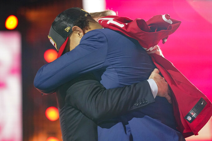 North Dakota State quarterback Trey Lance, right, embraces NFL Commissioner Roger Goodell after being chosen by the San Francisco 49ers with the third pick in the first round of the NFL football draft Thursday April 29, 2021, in Cleveland. (AP Photo/Tony Dejak)