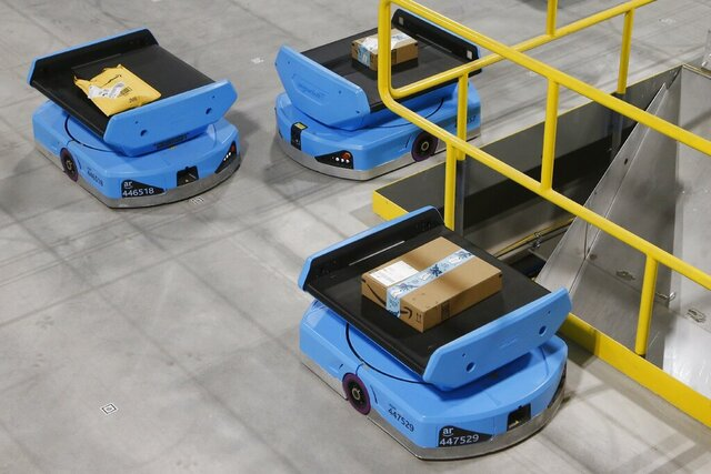 "In this Dec. 17, 2019, photo Amazon robots move along the warehouse floor with packages before finding the proper delivery chute, transporting packages from workers to chutes that are organized by zip code, at an Amazon warehouse facility in Goodyear, Ariz. Amazon and its rivals are increasingly requiring warehouse employees to get used to working with robots. The company now has more than 200,000 robotic vehicles it calls ""drives"" that are moving goods through its delivery-fulfillment centers around the U.S. (AP Photo/Ross D. Franklin)"