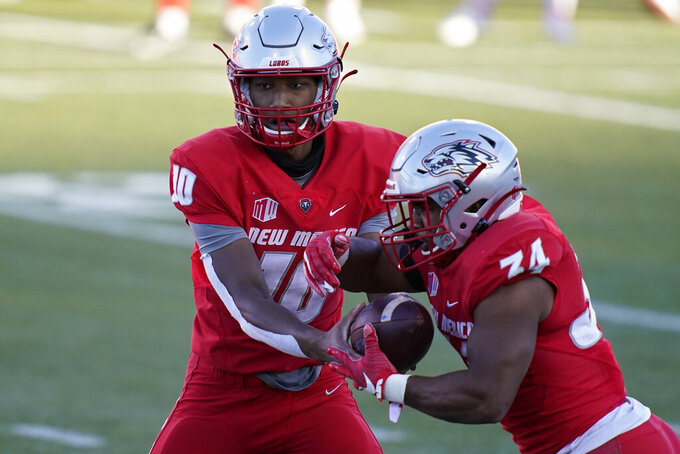 New Mexico quarterback Trae Hall (10) hands off the ball to running back Bobby Cole (34) during the first half of an NCAA college football game against Nevada, Saturday, Nov. 14, 2020, in Las Vegas. (AP Photo/John Locher)