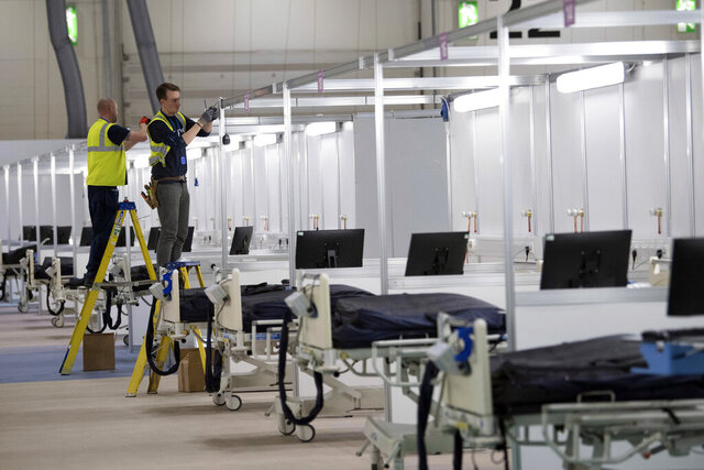 FILE - In this Tuesday, March 31, 2020 file photo work continues at the ExCel centre which is being made into a temporary hospital called NHS Nightingale in London. In the fight against the coronavirus pandemic, soldiers are delivering millions of face masks to hospitals and helping to build makeshift medical facilities, including one at London's ExCel convention center that can treat as many as 4,000 patients. (Stefan Rousseau/Pool Photo via AP, File)