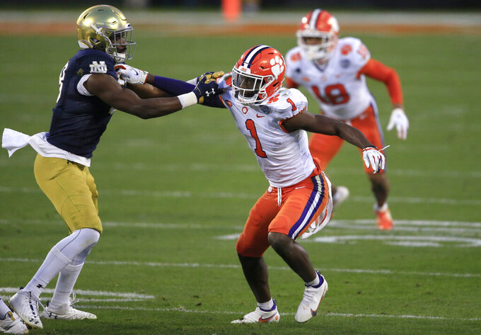 Clemson cornerback Derion Kendrick (1) tangles with Notre Dame wide receiver Javon McKinley (88) during the first half of the Atlantic Coast Conference championship NCAA college football game, Saturday, Dec. 19, 2020, in Charlotte, N.C. (AP Photo/Brian Blanco)