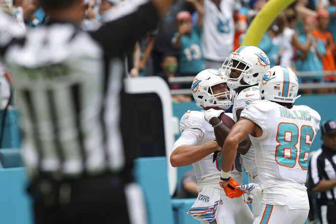 Miami Dolphins wide receiver Isaiah Ford (87) center celebrates scoring a touchdown, with teammates tight end Mike Gesicki (88), left, and wide receiver Mack Hollins (86), during the first half of an NFL football game, Sunday, Oct. 24, 2021, in Miami Gardens, Fla. (AP Photo/Hans Deryk)