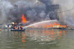In this handout photo provided by the Philippine Coast Guard, members of the Philippine Coast Guard use a rubber boat as they train their hose on a cargo ship docked in Manila, Philippines on Saturday, June 12, 2021. The fire and a powerful blast ripped through a small cargo ship docked to refuel in the Philippine capital of Manila on Saturday, injuring at least six people and igniting a blaze in a nearby riverside slum that gutted dozens of shanties, officials said. (Philippine Coast Guard via AP)
