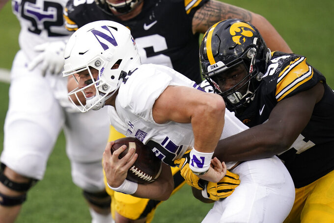 Northwestern quarterback Peyton Ramsey tries to break a tackle by Iowa defensive tackle Daviyon Nixon, right, during the second half of an NCAA college football game, Saturday, Oct. 31, 2020, in Iowa City, Iowa. (AP Photo/Charlie Neibergall)