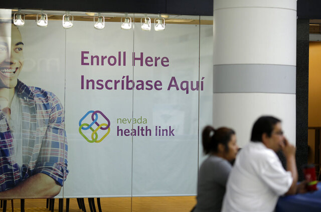 FILE - This Nov. 13, 2014 file photo people stand near an insurance store for Nevada Health Link at the Boulevard Mall in Las Vegas. Nevada's state-run health insurance marketplace added more than 6,000 people during a two-month window for those who lacked coverage but had not signed up during open enrollment last fall. (AP Photo/John Locher,File)