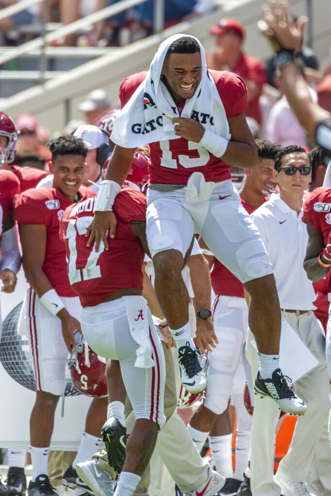 Alabama quarterback Tua Tagovailoa (13) leaps into the air to celebrate a 41-yard punt return by Alabama wide receiver Jaylen Waddle (17) during the second half of an NCAA college football game against Southern Miss, Saturday, Sept. 21, 2019, in Tuscaloosa, Ala. (AP Photo/Vasha Hunt)