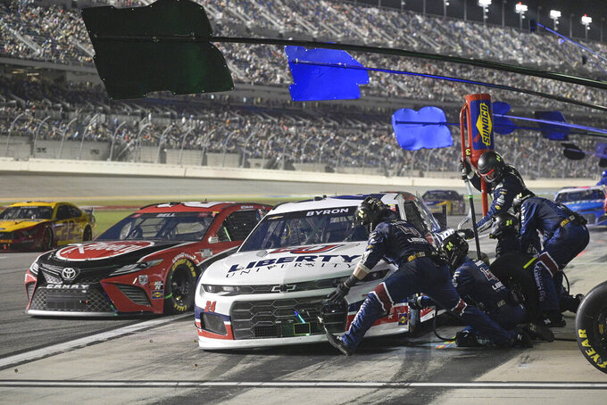 William Byron, right, pits as Christopher Bell, center, leaves his pit during the NASCAR Cup Series auto race at Daytona International Speedway, Saturday, Aug. 28, 2021, in Daytona Beach, Fla. (AP Photo/Phelan M. Ebenhack)