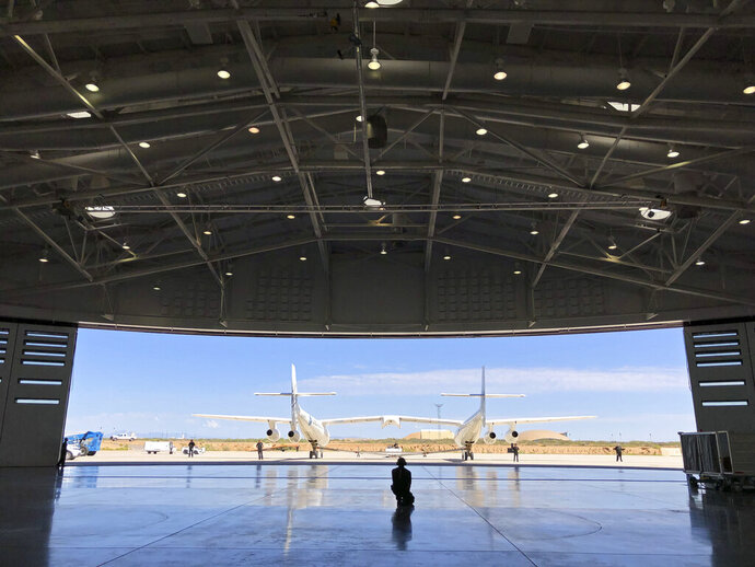 """FILE - In this Aug. 15, 2019 file photo, Virgin Galactic ground crew guide the company's carrier plane into the hangar at Spaceport America following a test flight over the desert near Upham, New Mexico. Virgin Galactic Holdings Inc. has agreed to a deal with NASA to boost commercial human spaceflight to the International Space Station and develop a """"robust economy"""" in space. (AP Photo/Susan Montoya Bryan, File)"""