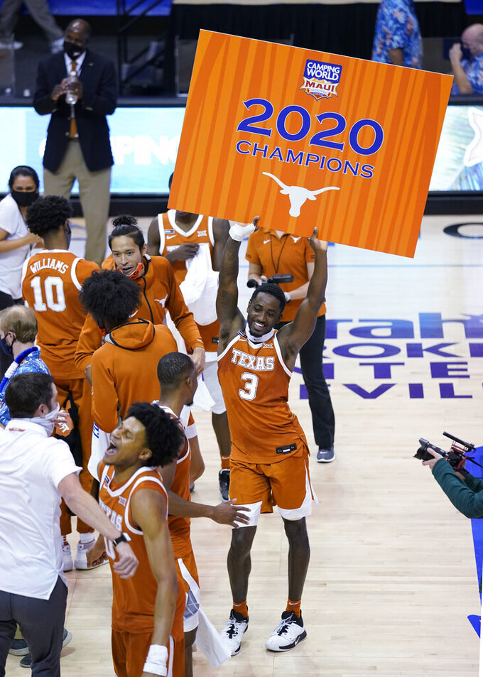 Texas guard Courtney Ramey (3) dances and holds a poster after the team's win over North Carolina in an NCAA college basketball game for the championship of the Maui Invitational, Wednesday, Dec. 2, 2020, in Asheville, N.C. (AP Photo/Kathy Kmonicek)