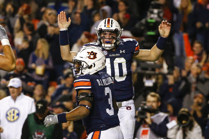 Auburn quarterback Bo Nix (10) celebrates after running back D.J. Williams (3) scored a touchdown during the first half of the team's NCAA college football game against Mississippi, Saturday, Nov. 2, 2019, in Auburn, Ala. (AP Photo/Butch Dill)