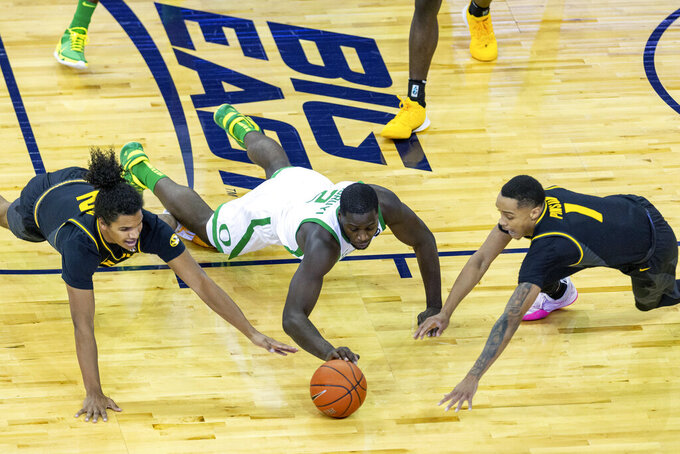 Missouri guard Dru Smith (12), Oregon forward Eugene Omoruyi (2), and Missouri guard Xavier Pinson (1) go after a loose ball during the first half of an NCAA college basketball game, Wednesday, Dec. 2, 2020 in Omaha, Neb. (AP Photo/John Peterson)