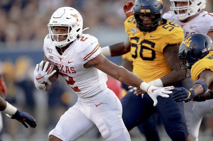 Texas running back Roschon Johnson (2) runs with the ball against West Virginia during an NCAA college football game on Saturday, Oct. 5, 2019, in Morgantown, W. Va. (Nick Wagner/Austin American-Statesman via AP)