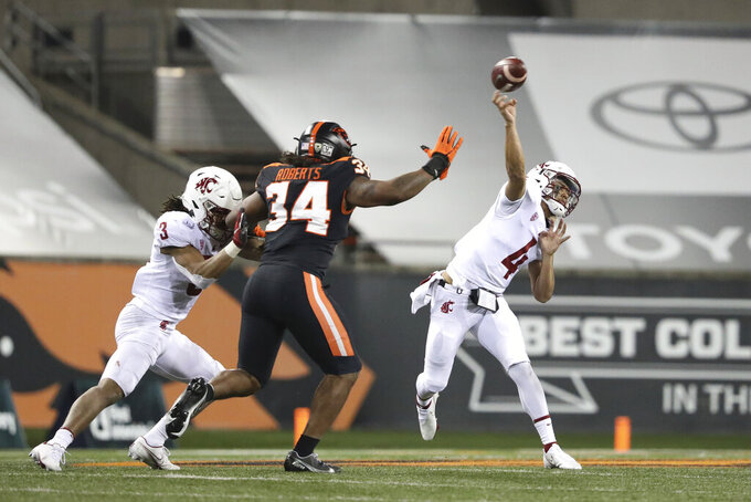 Washington State quarterback Jayden de Laura (4) throws past Oregon State inside linebacker Avery Roberts (34) and Washington State's Deon McIntosh (3) during the first half of an NCAA college football game in Corvallis, Ore., Saturday, Nov, 7, 2020. (AP Photo/Amanda Loman)