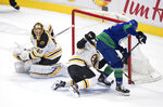 Vancouver Canucks' Loui Eriksson, right, of Sweden, scores a goal as Boston Bruins goalie Tuukka Rask (40), of Finland, watches and Matt Grzelcyk defends during the second period of an NHL hockey game Saturday, Feb. 22, 2020, in Vancouver, British Columbia. (Darryl Dyck/The Canadian Press via AP)