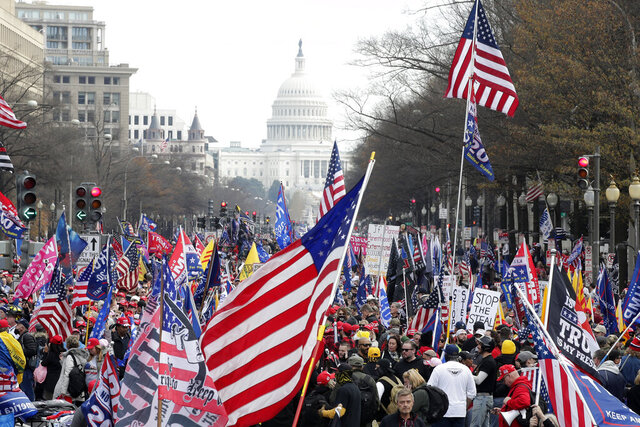 With the U.S. Capitol building in the background, supporters of President Donald Trump stand Pennsylvania Avenue during a rally at Freedom Plaza, Saturday, Dec. 12, 2020, in Washington. (AP Photo/Luis M. Alvarez)