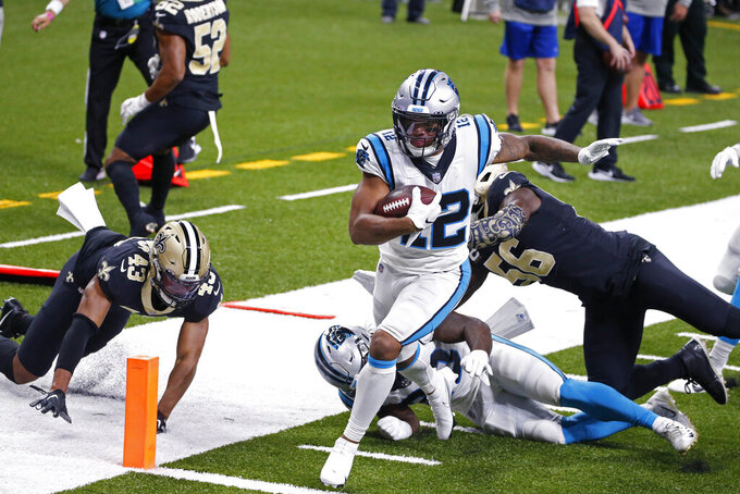 Carolina Panthers wide receiver D.J. Moore (12) crosses the goal line in front of New Orleans Saints outside linebacker Demario Davis (56) and free safety Marcus Williams (43) in the first half of an NFL football game in New Orleans, Sunday, Oct. 25, 2020. (AP Photo/Butch Dill)