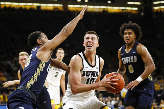 Iowa guard Joe Wieskamp (10) drives to the basket between Oral Roberts' Sam Kearns, left, and Kevin Obanor, right, during the second half of an NCAA college basketball game, Friday, Nov. 15, 2019, in Iowa City, Iowa. (AP Photo/Charlie Neibergall)
