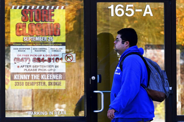 FILE - In this Friday, Nov. 6, 2020, file photo, a man walks past a closed store in Wilmette, Ill., amid the coronavirus pandemic. Responses to the coronavirus pandemic and police brutality dominated legislative sessions in 2020 and led to many new laws that will take effect in the new year. (AP Photo/Nam Y. Huh, File)